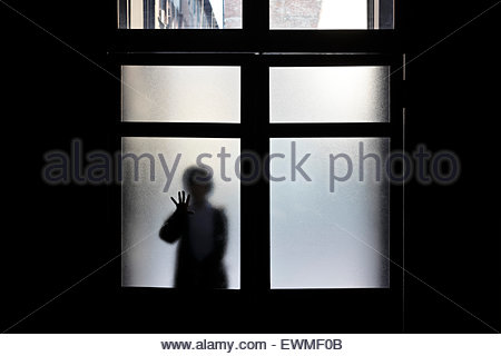 silhouetted woman entering a dark space seen through frosted glass - Stock Photo
