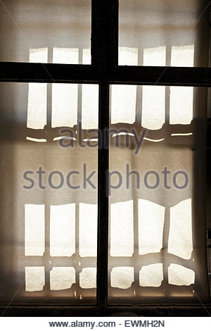 strong sunlight projection of an old style metal grating on curtain screen outside of the window - Stock Photo