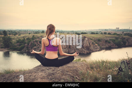 Young woman practicing yoga on the hill at sunset near the river. - Stock Photo