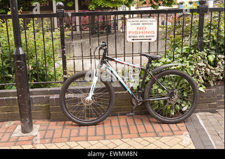 mountain bike chained up to metal railing in center of Chelmsford shopping centre next to river Chelmer and no fishing - Stock Photo