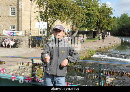 A man takes a  photograph of himself with a 'selfie stick' on a bridge in Bakewell, Peak District Derbyshire England - Stock Photo
