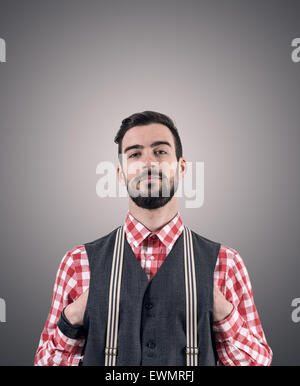 Desaturated portrait of young bearded hipster with hands pushed in his vest over dark gray studio background with - Stock Photo