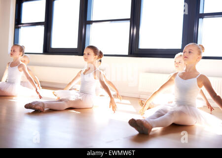 Group of cute graceful little ballerinas in class sitting on the wooden floor of the studio practising a pose with - Stock Photo