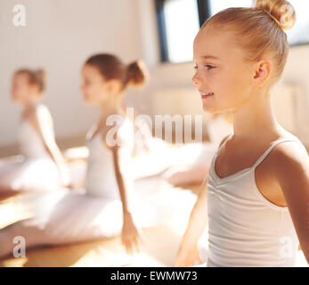 Close up side view of the face of a cute pretty little blond ballerina smiling in class as she practices her poses - Stock Photo