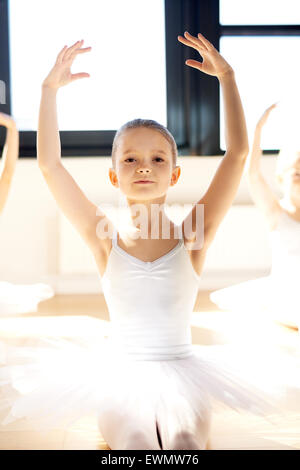 Graceful pretty little ballerina posing with raised arms in her white tutu in a bright sunlit dance studio as she - Stock Photo