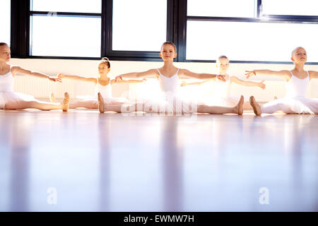 Group of little girls in a ballet studio wearing white tutus sitting on the floor practising with their arms raised - Stock Photo