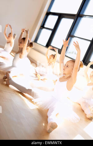Cute Young Ballet Girls in a Training Exercise, with Legs Open and Arms Up While Sitting on the Floor, Inside the - Stock Photo