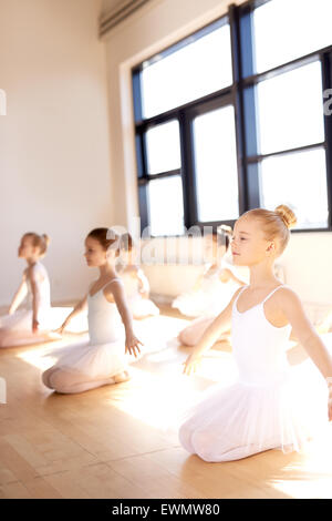 Pretty Little Ballet Girls Sitting on their Ankles with Arms Open for Stretching Exercise Inside the Dance Studio. - Stock Photo