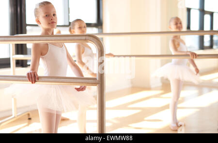 Group of young ballerinas in training at a classical ballet studio standing practicing together at the bar - Stock Photo