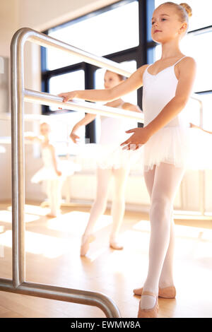 Graceful young girl practicing her ballet in a classical dance studio standing posing at the bar in her white tutu - Stock Photo