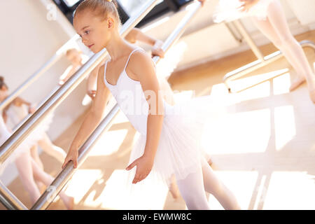 Young ballerina in ballet school practicing at the bar with her classmates in her white tutu, close up view - Stock Photo