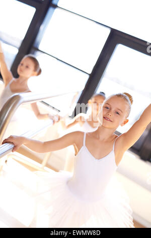 Pretty smiling young ballerina in training using the bar in the ballet school studio to practice her positions and - Stock Photo