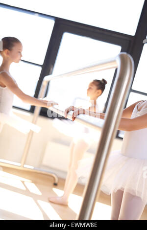 Pretty Little Ballerinas in White Tutu Holding Ballet Bar During their Training Exercise at the Studio. - Stock Photo