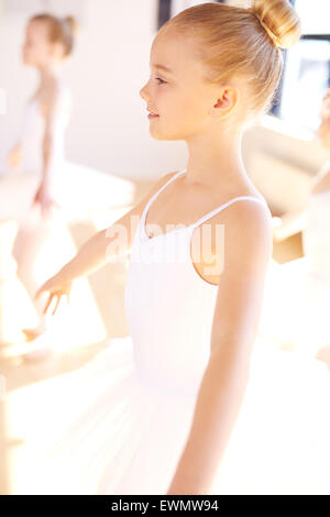 Close up Smiling Pretty Little Ballet Girl in White Tutu at the Dance Training Inside the Studio. - Stock Photo