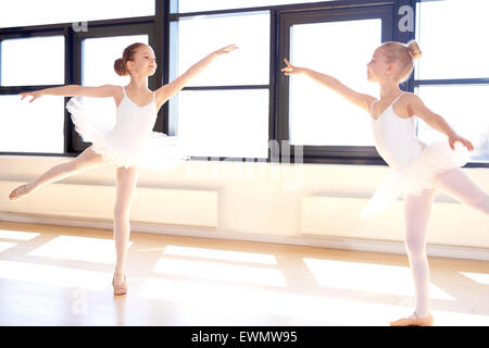 Two graceful little girls practicing a choreographed ballet in a classical ballet studio as they fulfil their dreams - Stock Photo
