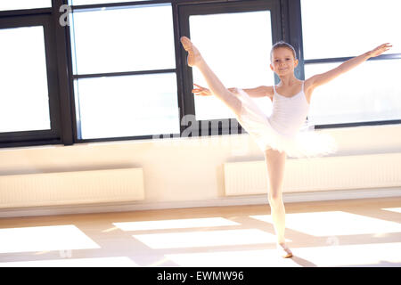 Agile pretty young ballerina practicing her positions in a graceful pose in front of bright windows at a ballet - Stock Photo
