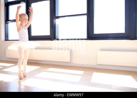 Little girl training to be a ballerina standing in a graceful arms raised position in her white tutu and pink satin - Stock Photo