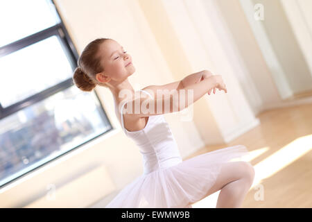 Smiling Pretty Ballet Girl in White Tutu Practicing a Dance Number Inside the Studio Alone. - Stock Photo