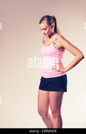Young woman wearing workout clothes with hands on hips and looking down. - Stock Photo