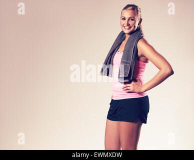 Young woman wearing workout clothes posing with hand on hip and smiling at camera. - Stock Photo