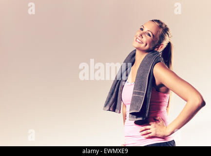 Young woman wearing workout clothes with hands on hops and head tilted back smiling. - Stock Photo