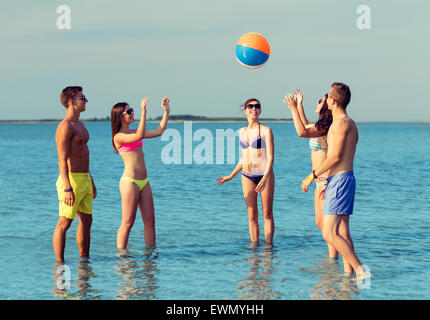 smiling friends in sunglasses on summer beach - Stock Photo