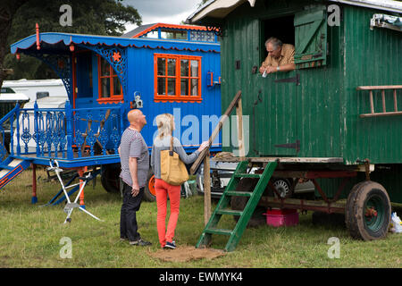 UK, England, Cheshire, Chelford, Astle Park Traction Engine Rally, visitors talking to man in old wooden caravan - Stock Photo