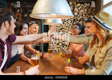 happy friends with drinks making high five at bar - Stock Photo