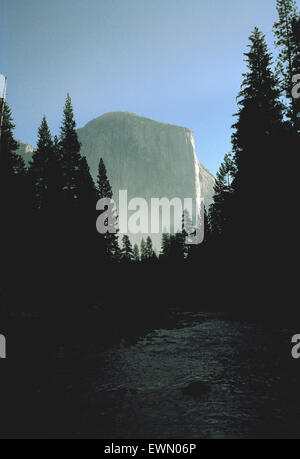 View of El Capitan in the mist along the Merced River at sundown in Yosemite National Park - Stock Photo