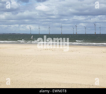 A windsurfer sails in front of an offshore wind farm in the River Tees estuary photographed from Redcar beach. - Stock Photo