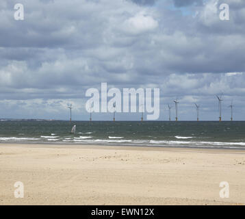 Offshore wind farm in the River Tees estuary photographed from Redcar beach. Windsurfer in the foreground - Stock Photo