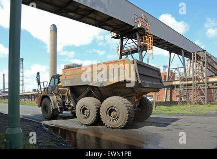 A specialist truck carries waste material beneath a conveyor gantry at the newly reopened Redcar Steel works, UK - Stock Photo