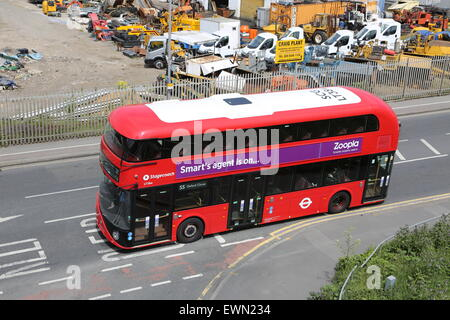 High level view of one of London's new Routmaster double-deck buses. Shown passing a contractors yard on Lea Bridge - Stock Photo