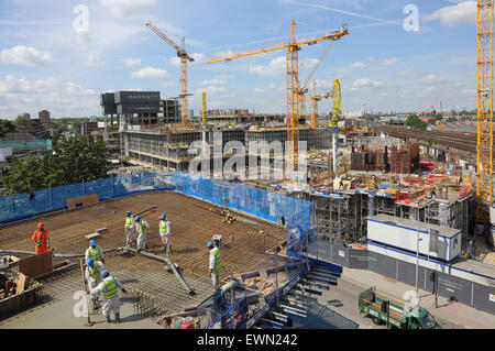 Workmen pour concrete on a new residential development at Vauxhall, London while another huge project is built in - Stock Photo