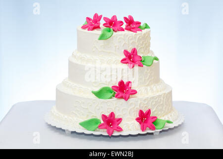 Three-storied white wedding cake with pink marzipan flower decoration - Stock Photo