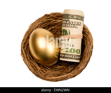 Gold egg sitting next to roll of currency or money.  Shot on white background. - Stock Photo
