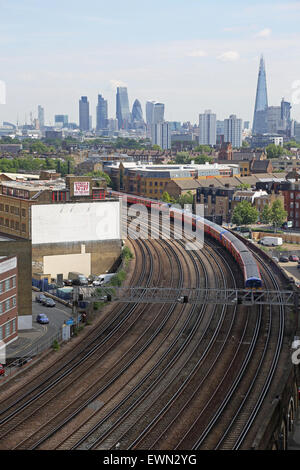 trains on rail tracks close to London's Vauxhall station with the skyline of the City of London in the background - Stock Photo