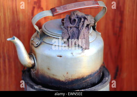 Old aluminum teapot on a street at the entry to traditional tibetan house in the lower area of town. Gyantse city - Stock Photo