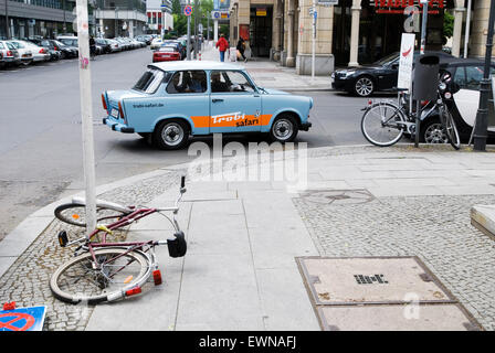 Streetscene with broken bicycle and trabant in Berlin Germany Europe - Stock Photo