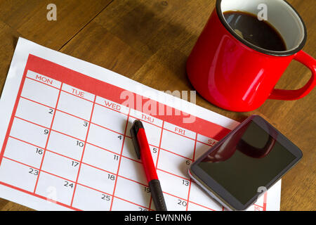 Organizing monthly activities and appointments in the calendar - Stock Photo
