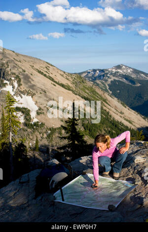 Woman using a map and electronic compass while backpacking in the Montana mountains. - Stock Photo