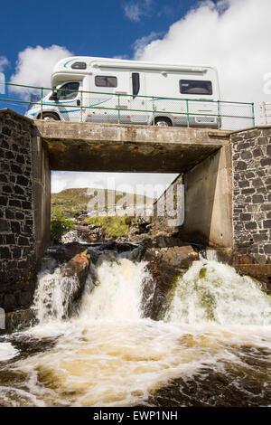 A camper van crossing a bridge over the Abhainn Eadarra amongst rugged mountain scenery on North East Harris, Outer - Stock Photo