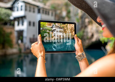 Woman photographing house on Buna spring in Blagaj village - Stock Photo