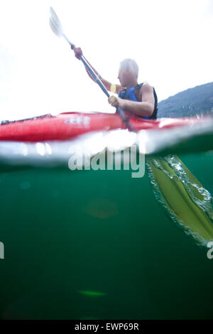 Over under water view of sea kayaker paddling on a lake - Stock Photo