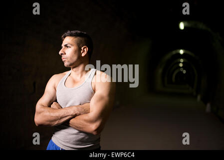Attractive young man posing in tunnel with tank top - Stock Photo