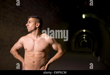 Young latin man posing in tunnel without shirt - Stock Photo