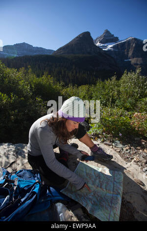 A woman reading a map in the high country. - Stock Photo