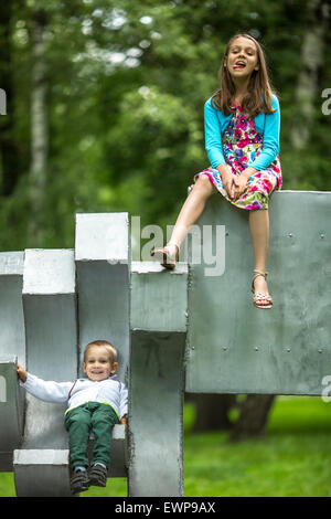 Girl with her little brother on the Playground in city Park. - Stock Photo
