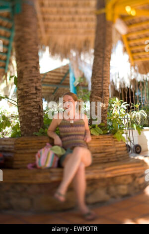 woman sitting beneath palapa in Mexico - Stock Photo