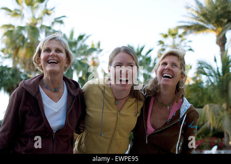 Three women laughing while on vacation - Stock Photo